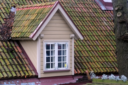 mansard: Attic with new siding and old tiled roof in Tallinn in Estonia Stock Photo