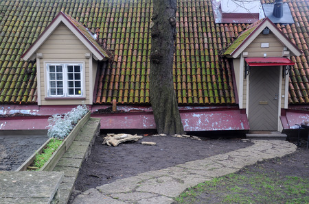 Part of the house with attic, entrance and old tiled roof in Tallinn in Estonia photo