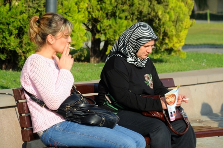 injurious: IZMIR, TURKEY - OCTOBER 1, 2009: Two Turkish women smoke on the bench in the city of Izmir in Turkey