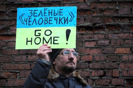 MOSCOW, RUSSIA – MARCH 15, 2014: Inidentified man protests holding Go Home sign during Moscow peace rally against Crimean referendum and further occupation of the peninsula Editorial