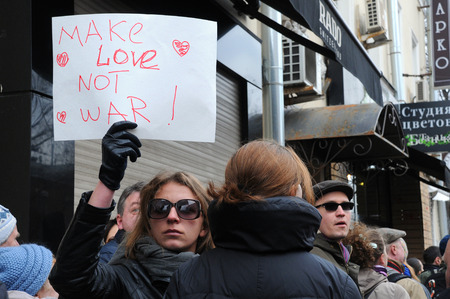 backlash: MOSCOW, RUSSIA � MARCH 15, 2014: Unidentified girl protests holding Make Love Not War sign during Moscow peace rally against Crimean referendum and further occupation of the peninsula