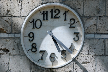 arabic numerals: Partially shaded old clock face with Arabic numerals on the building