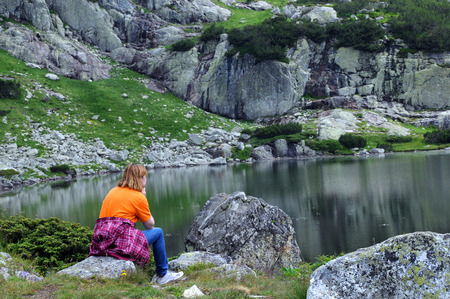 rocky mountain juniper: Caucasian woman sits on the stone and looks at the glacial Fish Lake in the Seven Lakes National Park in Bulgaria Stock Photo