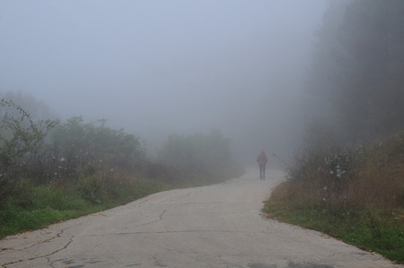Woman walks down the road on the foggy morning Stock Photo