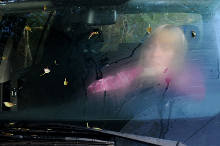 Blurry portrait of the middle-aged woman looking through the car fogged windshield Stock Photo