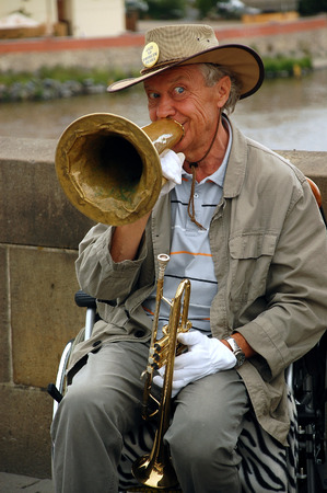 wheel chair: PRAGUE, CZECH REPUBLIC  JUNE 14, 2008: Famous in Prague stiff-limbed street musician plays jazz on the Charles bridge in the capital of Czechia Prague while sitting on the wheel chair Editorial