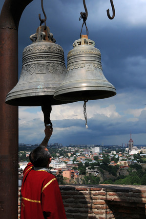 knell: TBILISI GEORGIA  JUNE 13 2015: Bellman rings the bells at the Saint Nicholas temple in Narikala fortress
