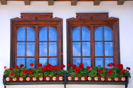 Two windows decorated with potted red flowers in Bulgaria