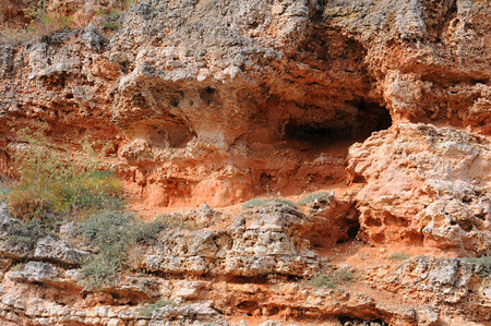 caved: Fragment of the red caved rock near Bolata beach in Dobrudja, Bulgaria