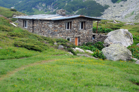 rocky mountain juniper: Stone building in the Rila mountains in Bulgaria Stock Photo