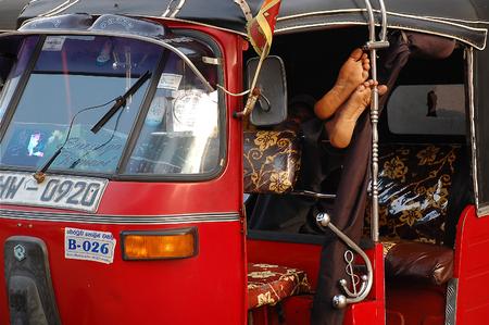 three wheeler: COLOMBO, SRI LANKA - DECEMBER 13, 2008: Three-wheeler driver takes a nap inside his tuk-tuk Editorial
