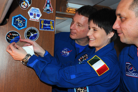 affix: MOSCOW, RUSSIA – NOVEMBER 11, 2014: ISS Expedition 4243 crewmembers T.Virts (left), S.Cristoforetti (center) and A.Shkaplerov (right) affix a decal aboard aircraft on the way to Baikonur cosmodrome