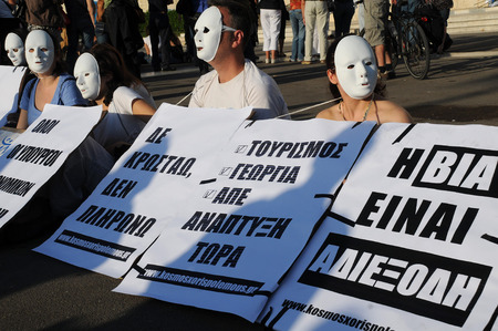 austerity: ATHENS, GREECE - MAY 9, 2010: Students wearing white masks protest in the capital of Greece Athens outside the Parliament building against unpopular EU-IMF austerity deal