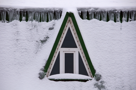 attic window: Attic window and icicles in snow on the building