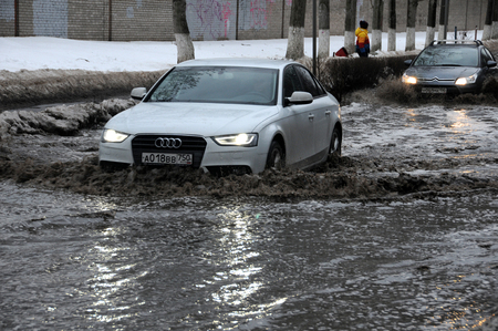 winter thaw: KOROLEV, RUSSIA - JANUARY 31, 2016: Cars drive down the flooded street after sudden thaw in the winter Editorial