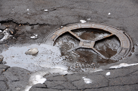 critical conditions: MOSCOW, RUSSIA - FEBRUARY 23, 2016: Sanitary sewer manhole in bad condition on the road in the winter
