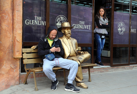 bulgaria girl: VELIKO TARNOVO, BULGARIA - MARCH 19, 2016: An unidentified Caucasian man and a girl next to the golden sitting statue of a gentleman