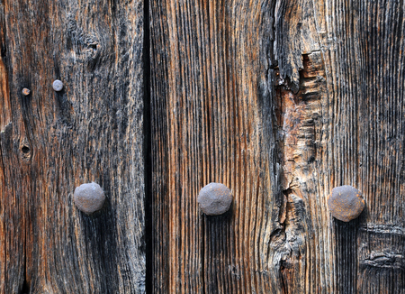 bolts heads: Old rusty bolts heads on the shabby wooden wall