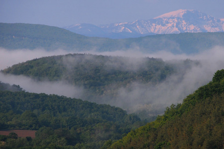 green ridge: View of the green hills and snowy mountain ridge in the background in the fog in Veliko Tarnovo province in Bulgaria in the month of May Stock Photo