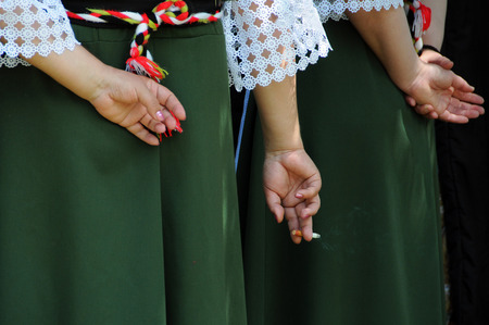 injurious: Hand with a cigarette in the fingers behind the ladys back