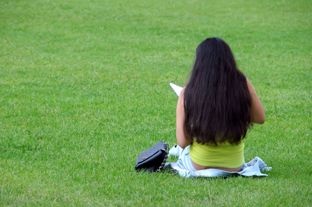An identified woman reads a book on the lawn