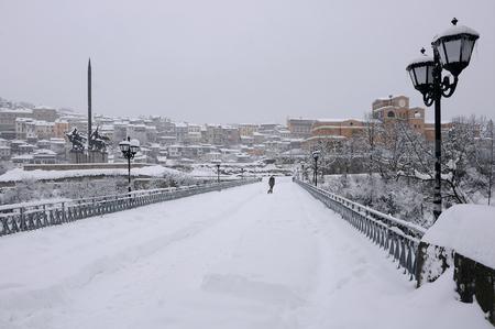 assen: VELIKO TARNOVO, BULGARIA - JANUARY 19, 2017: Woman walks her dog along the snowy bridge near the monument of Assens  on gloomy winter day