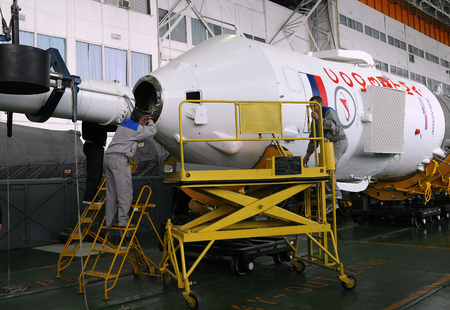 BAIKONUR COSMODROME, KAZAKHSTAN - DECEMBER 18, 2011: Soyuz spacecraft capsule is being mated with its booster rocket in the Integration facility building Editorial