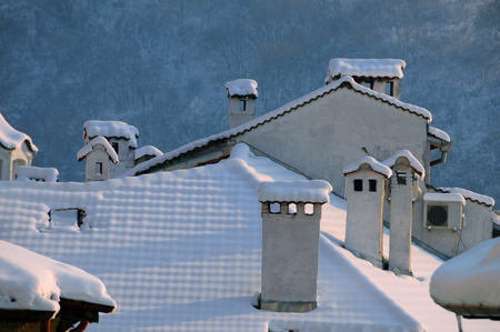 Snow-covered roof with many chimneys in the town of Veliko Tarnovo in Bulgaria Standard-Bild - 114404860