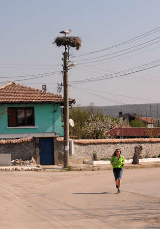 MOMIN SBOR VILLAGE, BULGARIA - APRIL 12, 2020: Stork in the nest and an unidentified girl doing jogging