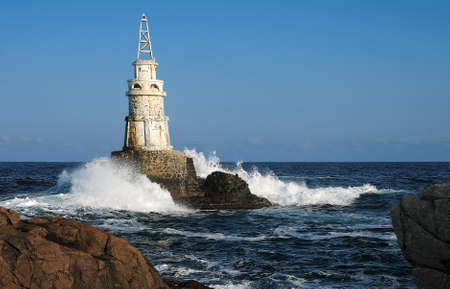View of the small light house and waves in the Black sea near the town of Akhtopol in Bulgaria