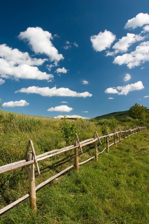 East European summer landcape with wooden fence and beautiful clouds Standard-Bild