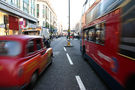 Black cab and coach passing on London street