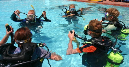Instructor and students during scuba diving lessons photo