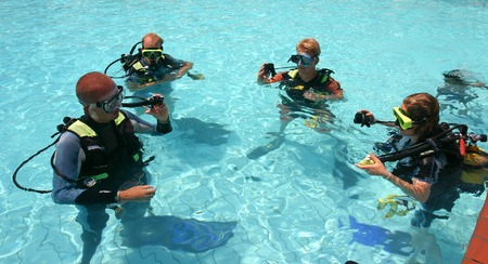 scuba goggles: Instructor and students during scuba diving lessons