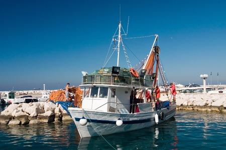 Few fishermans prepare shrimp boat to sail out Standard-Bild