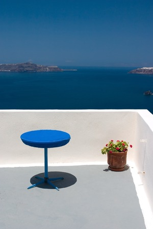 View from the balcony to Aegean Sea. Blue table and plant in vase standing on this balcony.