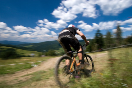 Male mtb biker during downhill event in motion blur