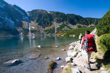 Couple trekking by the side of mountain pond in Tatra Mountains, Poland photo