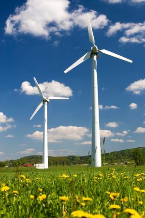 Windmills against blue sky with white clouds and yellow flowers on the ground Stock Photo