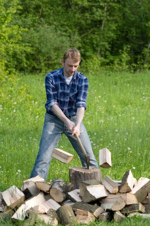 Young man is chopping wood
