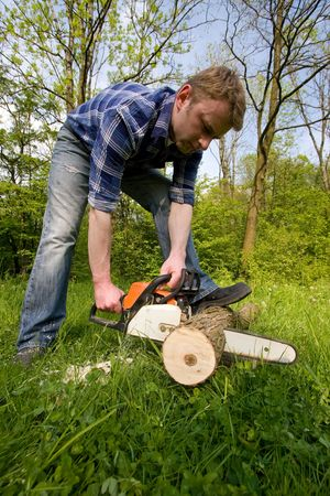 Young man cutting wood