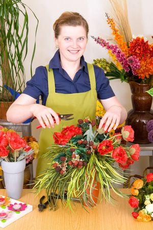 Young Florist in shop preparing flower decoration