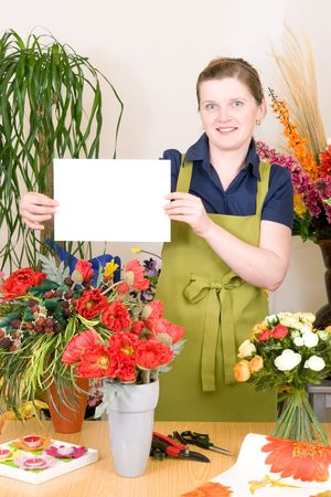 Young female florist holding white sign