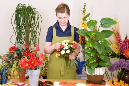 Young florist working on flower bouquet
