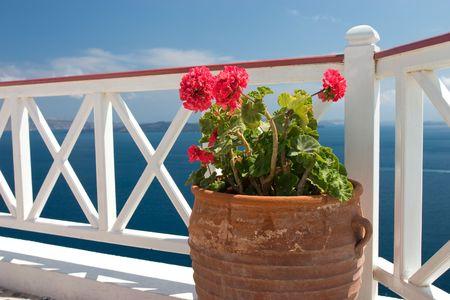 Vase with geraniums on the balcony in Greek island Santorini photo