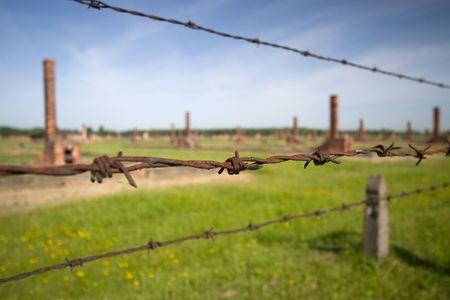 birkenau: Barbed wire and chimney in background, Auschwitz Birkenau
