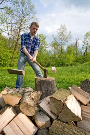 Wide angle view of young men preparing firewood Standard-Bild