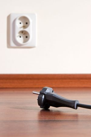 Two pin plug on the floor and electrical outlet in background Stock Photo