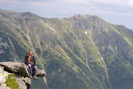 Young male is sitting on the edge of a precipice in Tatra Mountains, Slovakia Standard-Bild