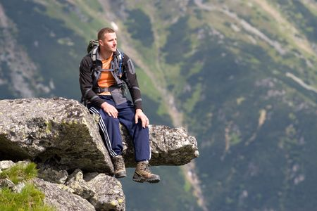 Young men is relaxing on the edge of precipice in Tatra Mountains, Slovakia Standard-Bild